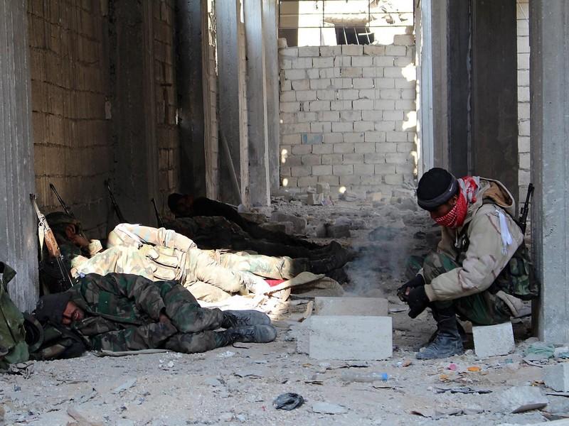 Quân chính phủ Syria nghỉ ngơi sau một cuộc giao tranh chiếm lại quận Sheil Saeed (đông Aleppo) ngày 12-12. Ảnh: EPA