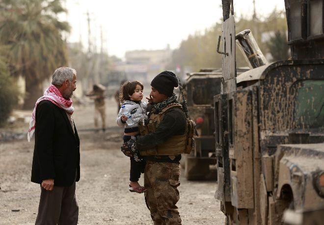 Lính chống khủng bố Iraq và người dân khu vực Mosul tái chiếm được từ IS ngày 13-12. Ảnh: AP