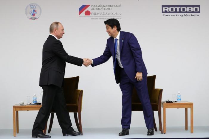 Tổng thống Putin (trái) bắt tay Thủ tướng Abe trong buổi đối thoại doanh nghiệp Nhật-Nga tại Tokyo (Nhật) ngày 16-12. Ảnh: REUTERS