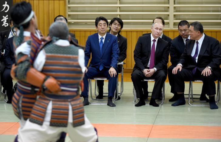 Tổng thống Putin (ngồi giữa), Thủ tướng Abe (trái), và Phó Chủ tịch Liên đoàn Judo Nhật Yasuhiro Yamashita (phải) xem biểu diễn judo tại Viện Judo Kodokan ở Tokyo (Nhật) ngày 16-12. Ông Putin vốn là một võ sĩ judo. Ảnh: RETERS