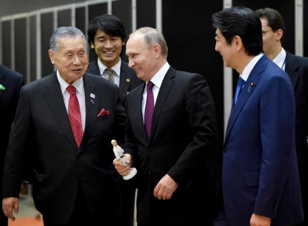 Tổng thống Putin (giữa) được tặng tượng người sáng lập môn võ Judo Jigoro Kano tại Viện Judo Kodokan ở Tokyo (Nhật) ngày 16-12. Ảnh: REUTERS