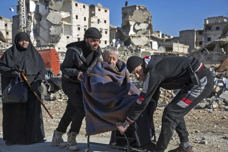 Người lớn tuổi được giúp đỡ đi sơ tán khỏi Aleppo ngày 15-12. Ảnh: AFP