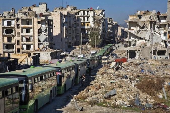 Hàng dài xe buýt chở người đi sơ tán khỏi Aleppo ngày 15-12. Ảnh: GETTY IMAGES
