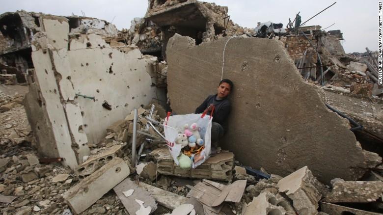 Cậu bé Syria cùng hành lý sơ tán ngồi trên đống đổ nát trước đó là nhà của mình ở quận Al-Arkoub (Aleppo) ngày 17-12. Ảnh: CNN