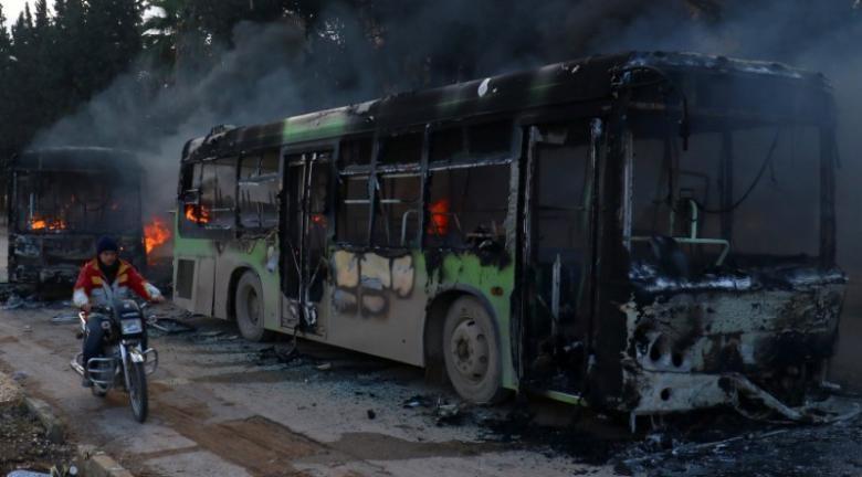 Xe buýt dùng chở người dân và phe nổi dậy sơ tán bị đốt gần tỉnh Idlib (Syria) ngày 18-12. Ảnh: REUTERS