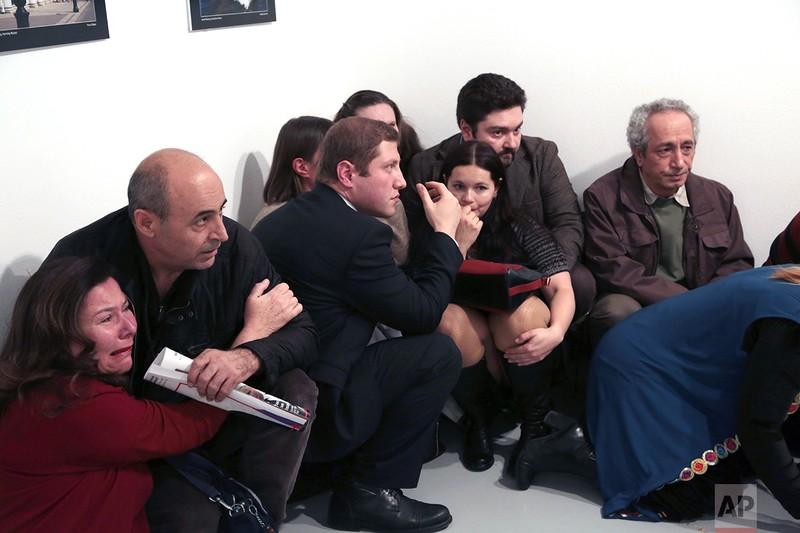 Khách tập trung tại một góc phòng sau khi đại sứ Andrei Karlov bị bắn ở phòng triển lãm ảnh ở Ankara (Thổ Nhĩ Kỳ) ngày 19-12. Ảnh: AP/ Burhan Ozbilici
