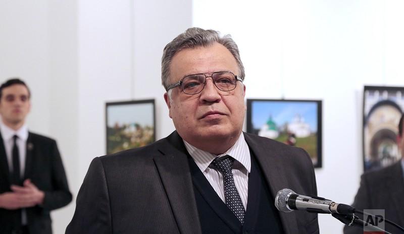 Đại sứ Andrei Karlov phát biểu tại phòng triển lãm ảnh trước khi bị bắn chết. Kẻ ám sát Mevlut Mert Altintas đứng ngay sau lưng đại sứ (bên trái). Ảnh AP/Burhan Ozbilici