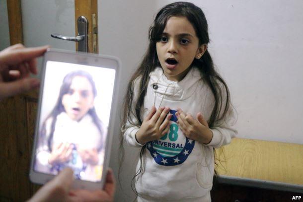 Cô bé Bana được mẹ quay phim lại trong khi cô bé đang trình bày bằng tiếng Anh về cuộc sống trong vùng chiến sự đông Aleppo ngày 12-10. Ảnh: TWITTER