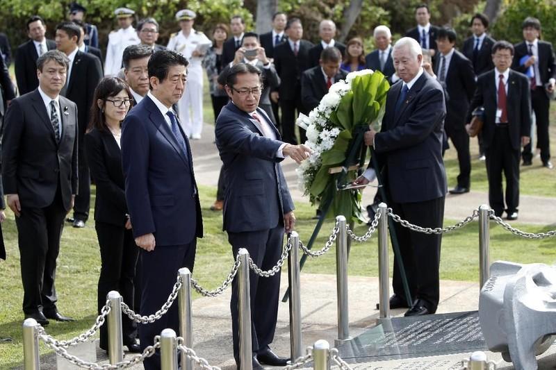 Thủ tướng Nhật Shinzo Abe (thứ ba từ trái sang) đặt vòng hoa tại đài tưởng niệm Ehime Maru ngày 26-12. Ảnh: AP