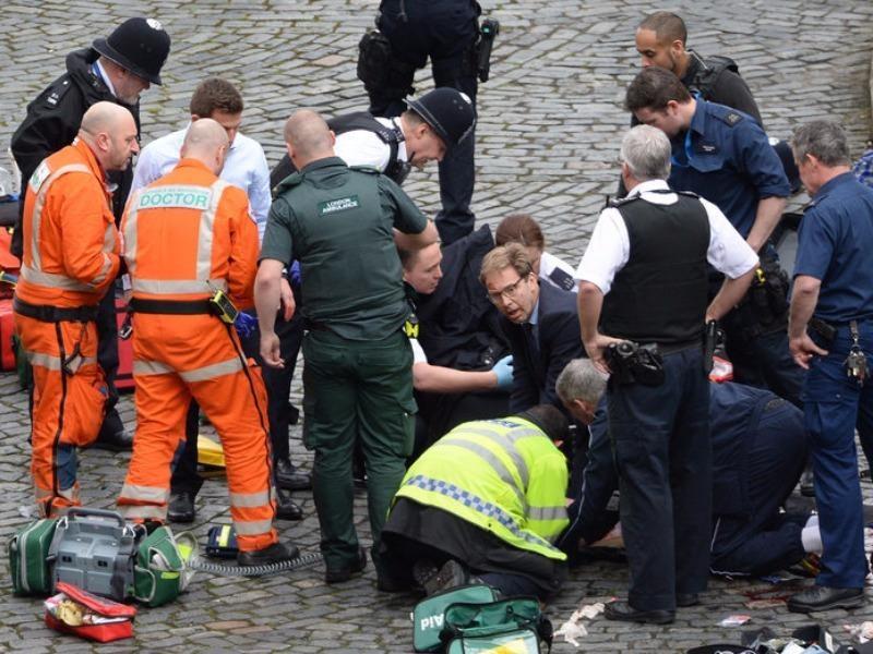Nghị sĩ Anh (mang kính) giúp cứu chữa người bị thương trên đường. Ảnh: PA
