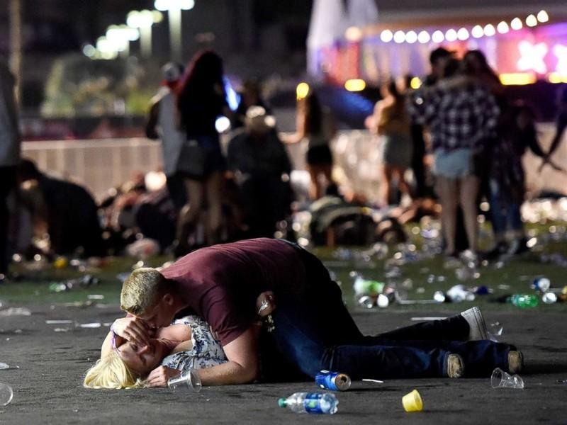 Một người đàn ông dùng thân mình che chở cho một phụ nữ tại hiện trường. Ảnh: GETTY IMAGES