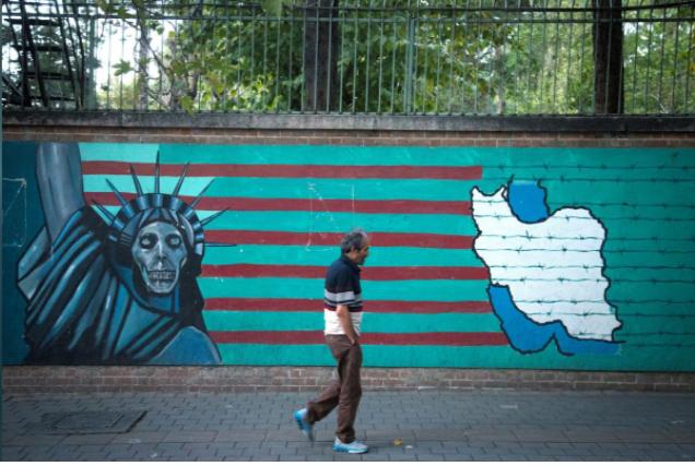 Người dân Iran bước ngang hình ảnh chống Mỹ ở Tehran (Iran) ngày 13-10. Ảnh: REUTERS