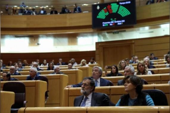 Thủ tướng Tây Ban Nha Mariano Rajoy (giữa) và Phó Thủ tướng nước này Soraya Saenz de Santamaria (phải) theo dõi kết quả bỏ phiếu của Thượng viện ngày 27-10 đồng ý biện pháp khẩn cấp tước quyền tự trị Catalonia. Ảnh: REUTERS