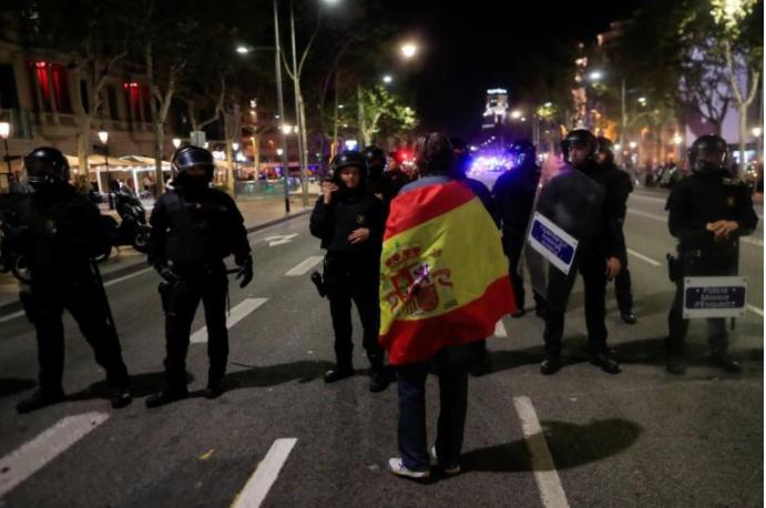 Cảnh sát Catalonia bảo vệ an ninh khi người ủng hộ độc lập xuống đường ăn mừng sau khi nghị viện Catalonia tuyên bố độc lập khỏi Tây Ban Nha, ngày 27-10. Ảnh: REUTERS