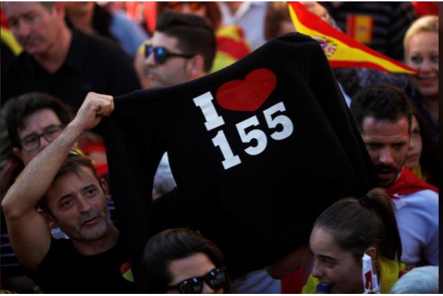 """Biểu ngữ """"Tôi yêu Điều 155"""" – cho phép chính phủ trung ương tước quyền tự trị Catalonia được người Catalonia mang trong cuộc biểu tình ủng hộ thống nhất, phản đối độc lập, ngày 29-10. Ảnh: REUTERS"""