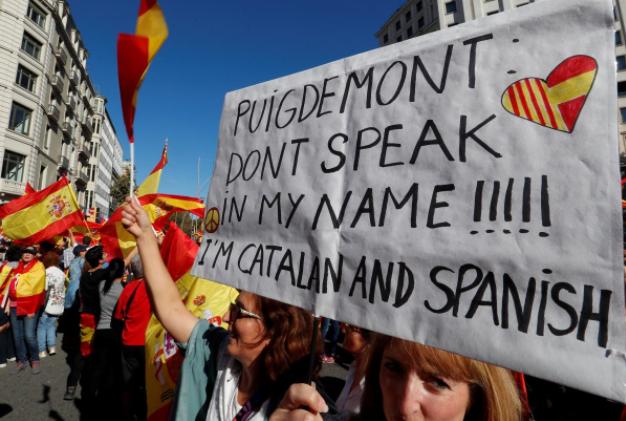 """Dân Catalonia mang biểu ngữ """"Ông Puigdemont, đừng nói nhân danh tôi"""", xuống đường ở Barcelona biểu tình ủng hộ thống nhất, phản đối độc lập, ngày 29-10. Ảnh: REUTERS"""