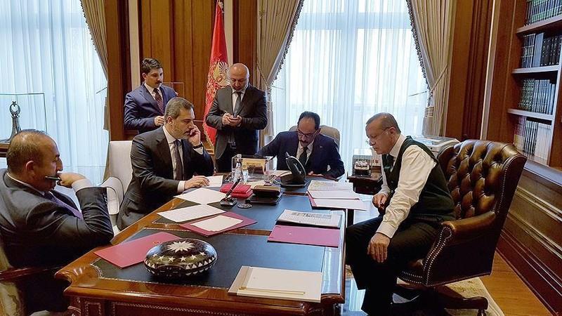 Tổng thống Thổ Nhĩ Kỳ Recep Tayyip Erdogan (ngồi phải) điện đàm với Tổng thống Mỹ Donald Trump ngày 24-11. Xung quanh ông là người phát ngôn tổng thống Ibrahim Kalin (ngồi giữa, phải), Giám đốc Cơ quan Tình báo Thổ Nhĩ Kỳ Hakan Fidan (ngồi giữa, trái), và Ngoại trưởng Thổ Nhĩ Kỳ Mevlut Cavusoglu (ngồi trái). Ảnh: ANADOLU AGENCY