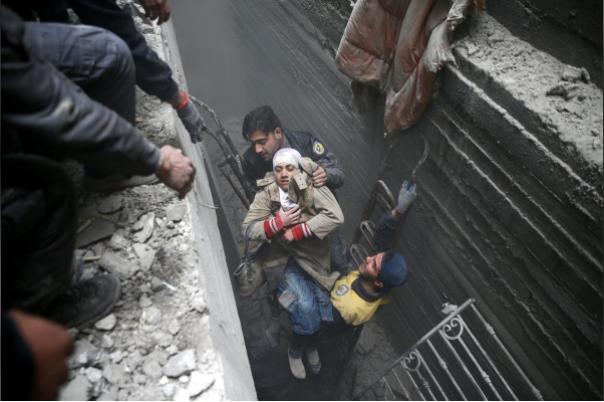 Cứu hộ một phụ nữ bị hôn mê từ dưới hầm trú ẩn ở thị trấn Douma, Đông Ghouta (Syria) ngày 22-2. Ảnh REUTERS