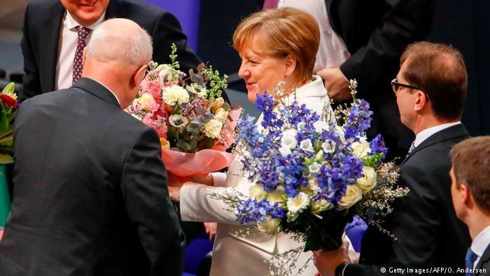Bà Merkel nhận hoa chúc mừng chiến thắng sáng 14-3. Ảnh: GETTY IMMAGES
