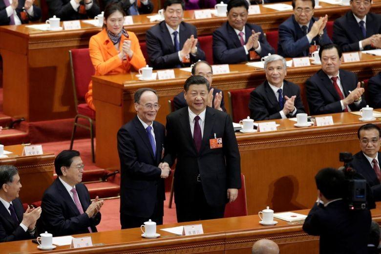Chủ tịch Trung Quốc Tập Cận Bình (giữa, phải) bắt tay tân Phó Chủ tịch Trung Quốc Vương Kỳ Sơn tại phiên họp thứ 5 kỳ họp Quốc hội thứ nhất ngày 17-3. Ảnh: REUTERS