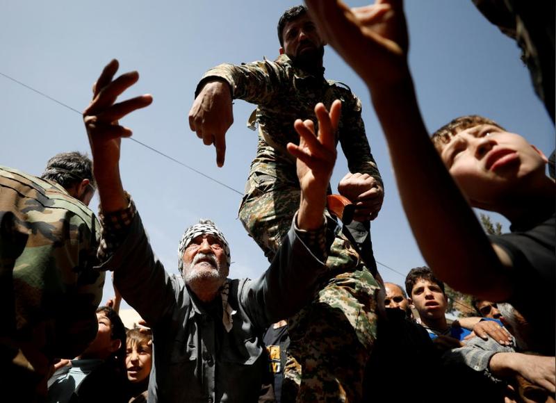 Người dân sơ tán từ Đông Ghouta nhận cứu trợ từ lực lượng của Nga ở Adra, gần Damacus (Syria) ngày 20-3. Ảnh: REUTERS