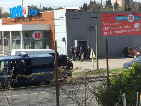 Cảnh sát bao vây ngoài cửa hàng nơi xảy ra vụ bắt cóc con tin tại thị trấn Trebes, tỉnh Aude thuộc vùng Occitania ở miền nam Pháp ngày 23-3. Ảnh: REUTERS