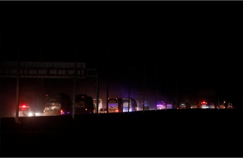 Đoàn xe chở các tay súng nổi dậy và người thân ở thị trấn Harasta, Đông Ghouta, ngoại ô thủ dô Damacus (Syria) rời đi vào chiều tối 22-3. Ảnh: REUTERS