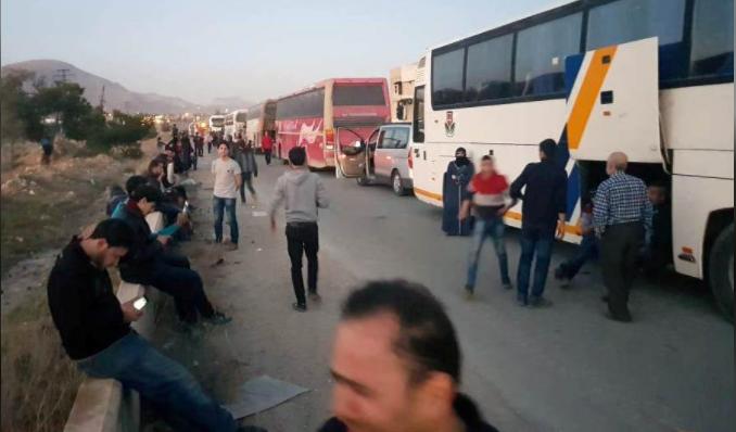Người dân thị trấn Douma chờ lên xe rời Đông Ghouta, ngoại ô thủ đô Damacus (Syria) ngày 1-4. Ảnh: REUTERS