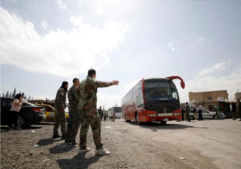 Các tay súng nổi dậy cuối cùng và người thân rút khỏi Douma, Đông Ghouta (Syria) – nơi xảy ra nghi án tấn công hóa học khuya 7-4. Ảnh: REUTERS