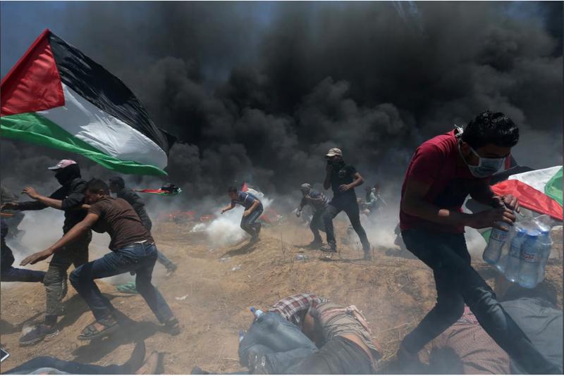 Người Palestine oằn mình trong đạn khói của binh sĩ Israel trong cuộc biểu tình tại biên giới Dải Gaza-Israel ngày 14-5. Ảnh: REUTERS