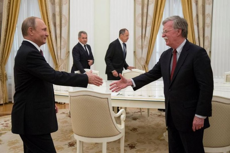 Tổng thống Nga Vladimir Putin (trái) bắt tay Cố vấn an ninh quốc gia Mỹ John Bolton trong cuộc gặp tại Điện Kremlin (Nga) ngày 27-6. Ảnh: REUTERS