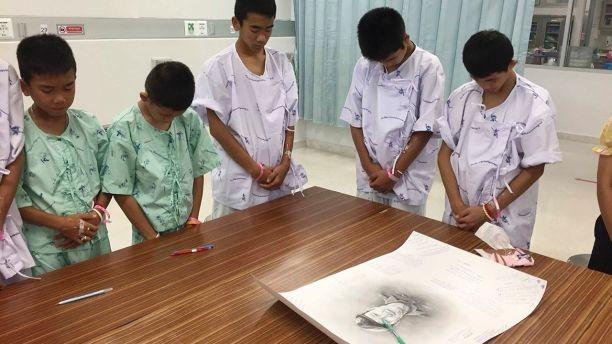Các cậu bé cúi đầu tưởng niệm thợ lặn Saman Kunan, cựu đặc nhiệm hải quân Thái Lan thiệt mạng vì thiếu ô xy trong quá trình lặn lắp đặt bình ô xy dọc hang động chuẩn bị cho công tác giải cứu. Ảnh: AP