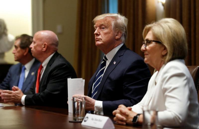 Ông Trump ngồi giữa hai nghị sĩ Cộng hòa trong cuộc trao đổi với một số nghị sĩ Mỹ và báo chí tại Nhà Trắng ngày 17-7. Ảnh: REUTERS