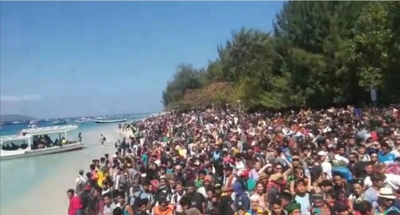Người dân kéo ra bờ biển chờ rời đảo Lombok (Indonesia) ngày 6-8, sau khi địa phương xảy ra động đất mạnh 6,9 độ Richter tối 5-8. Ảnh: REUTERS