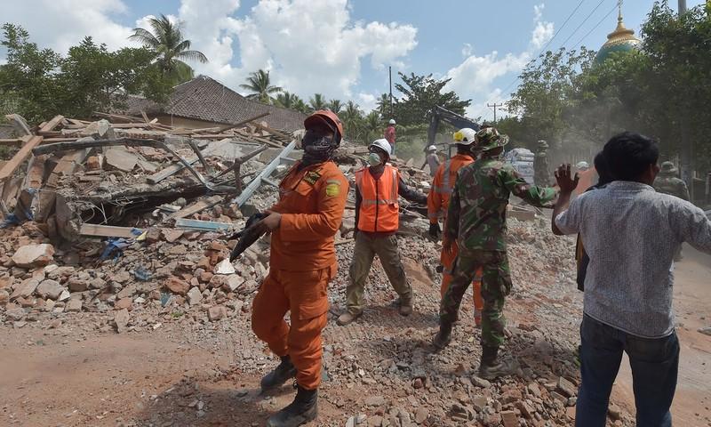 Các nhân viên cứu hộ khôi phục tìm kiếm người mất tích trong các đống đổ nát, không lâu sau khi trận động đất thứ ba xảy ra trưa 9-8. Ảnh: AFP