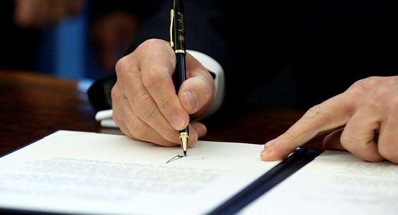 Tổng thống Mỹ Donald Trump ký thông qua Đạo luật Ủy quyền Quốc phòng tài khóa 2019 ngày 13-8. Ảnh: REUTERS