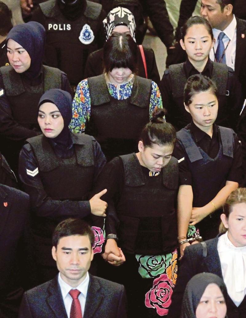 Các nghi can Siti Aisyah (giữa, hàng đầu) và Đoàn Thị Hương (giữa, hàng thứ hai) bị cảnh sát dẫn đến hiện trường vụ án ở sân bay quốc tế Kuala Lumpur (Malaysia) ngày 24-10-2017. Ảnh: NEW STRAIT TIMES