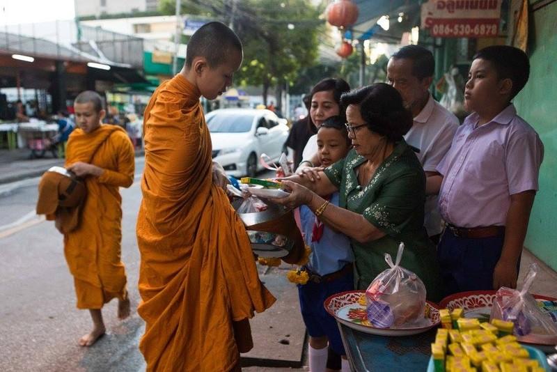 Một nhà sư trẻ đang nhận thức ăn từ các tín đồ Phật giáo. Ảnh: NEW YORK TIMES
