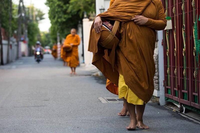 Các nhà sư đang đi khất thực trên một con đường tại thủ đô Bangkok, Thái Lan. Ảnh: NEW YORK TIMES