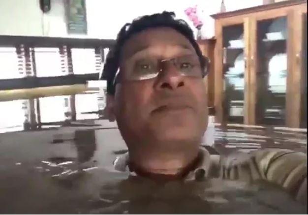 Người dân chụp hình mình đang mắc kẹt trong ngôi nhà lụt và kêu cứu. Ảnh: GUARDIAN