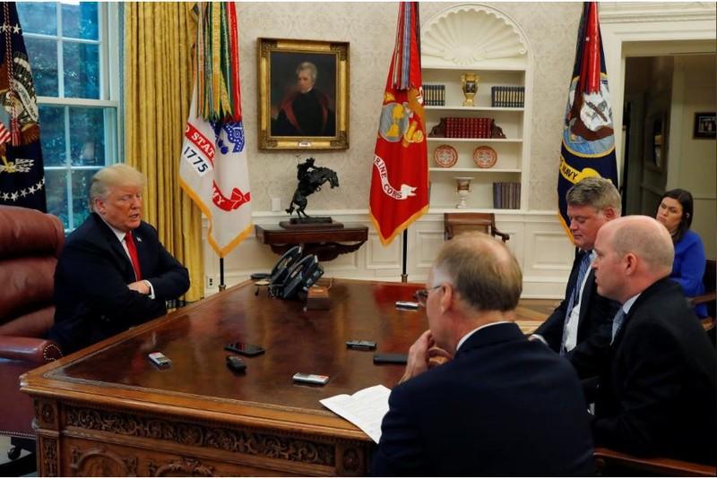 Tổng thống Mỹ Donald Trump (trái) trong buổi trả lời phỏng vấn các nhà báo Reuters tại Nhà Trắng ngày 20-8. Người phát ngôn Nhà Trắng Sarah Sanders (áo xanh) ngồi đằng sau. Ảnh: REUTERS