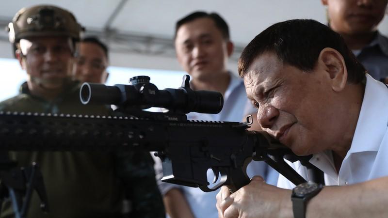 Ông Duterte bên một khẩu súng trường. Mỹ từ chối bán súng trường tấn công cho Philippines. Ảnh: AFP
