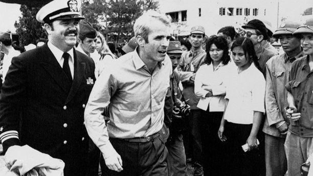 Cựu binh John McCain (giữa) được hộ tống đến sân bay ở Hà Nội để về Mỹ, ngày 14-3-1973. Ảnh: AP