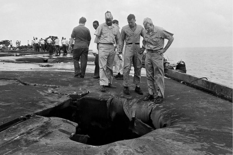 Thiếu tá hải quân John McCain (phải) cùng các đồng nghiệp Robert Browning (trái), Kenneth McMillen (giữa) xem xét hư hại trên con tàu sân bay USS Forrestal – nơi đã xảy ra tại nạn nghiêm trọng tháng 7-1967 giết chết 134 và làm bị thương 161 thủy thủ trên tàu. Phi công McCain đã may mắn thoát được. Ảnh: GETTY IMAGES