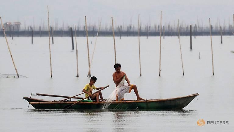 Ngư dân thu lưới trước bão Mangkhut tại khu vực đánh bắt cá ở hồ Laguna de Bay, đảo Luzon (Philippines) ngày 14-9. Ảnh: REUTERS