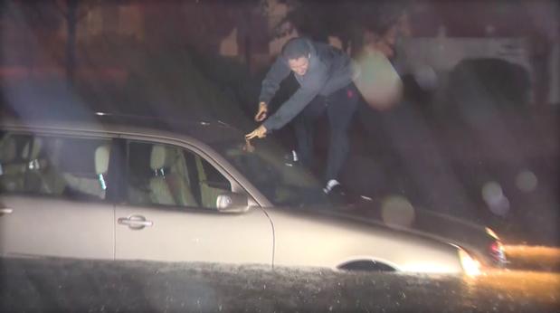 Người dân cố thoát ra khỏi một chiếc xe ngập trong nước ở TP Wilmington, bang North Carolina (Mỹ). Ảnh: CBS NEWS