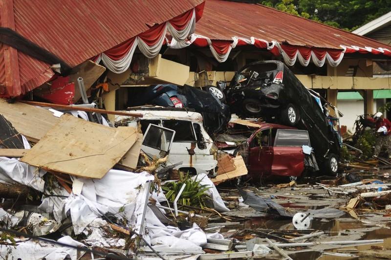 Nhà cửa, xe cộ hư hại ở Palu, Trung Sulawesi (Indonesia) ngày 30-9. Ảnh: JAKARTA POST