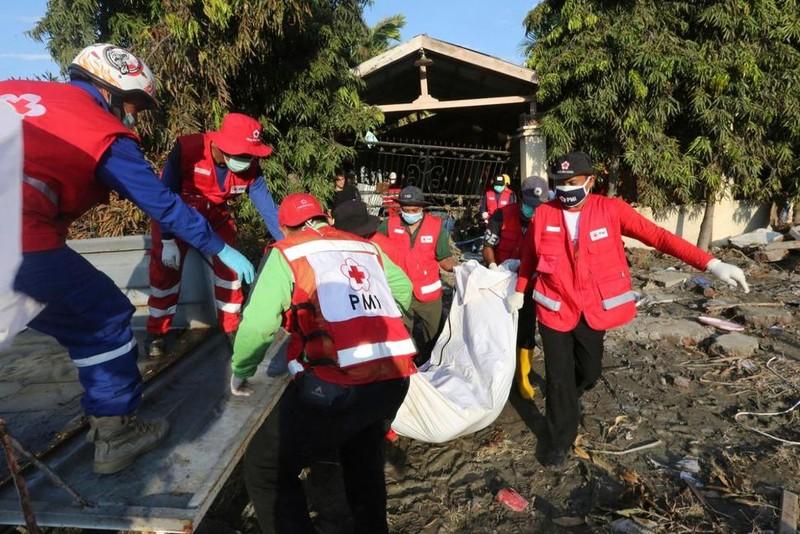 Nhân viên Hội Chữ thập đỏ Indonesia mang thi thể nạn nhân đi chôn tập thể tại Palu ngày 1-10. Ảnh: AP