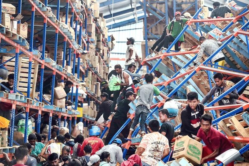 Người dân đột nhập cướp một nhà kho ở bắc Palu, Trung Sulawesi (Indonesia) ngày 1-10, Ảnh: ANTARA