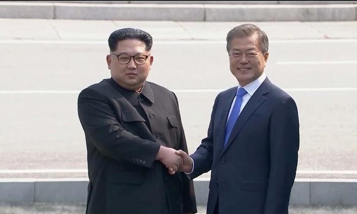 Cú bắt tay lịch sử giữa Tổng thống Hàn Quốc Moon Jae-in (phải) và lãnh đạo Triều Tiên Kim Jong-un tại làng Bàn Môn Điếm trong cuộc gặp thượng đỉnh đầu tiên sáng 27-4. Ảnh: REUTERS